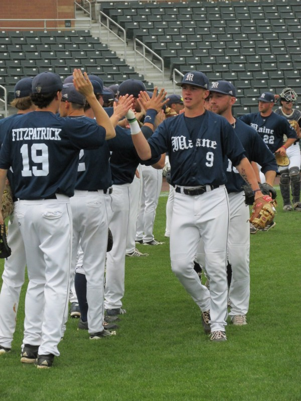 University of Maine players including Burk FitzPatrick (left) and Shane Bussey (9) go through a line of high-fives after taking infield practice prior to Wednesday's league playoff game against Stony Brook at Lowell, Mass. Maine went on to beat Stony Brook 7-0.