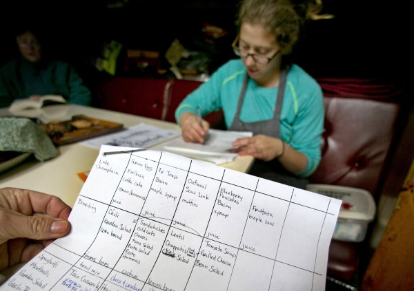 Cook Dani Hammond, of Peoria, Ill., prepares her shopping list after filling in the calendar's with each day's meals for an upcoming 5-day cruise. She uses a wood stove to prepare everything from blueberry pancakes to honey-ginger chicken.