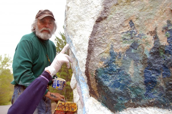 Nancy Meader points to a spot her husband Abbott missed as they repaint the mural on Pockwockamus Rock on Wednesday.