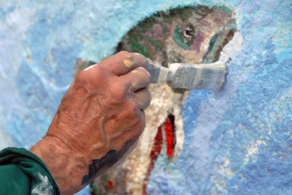 Abbott Meader of Oakland touches up the mural first painted in 1979 onto Pockwockamus Rock about a mile from the south gate to Baxter State Park on Wednesday.