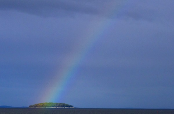 A weekend of rainy weather begins to clear up as a rainbow touches down over Mark Island in Penobscot Bay, as viewed from the schooner Mary Day off Rockland, Maine.