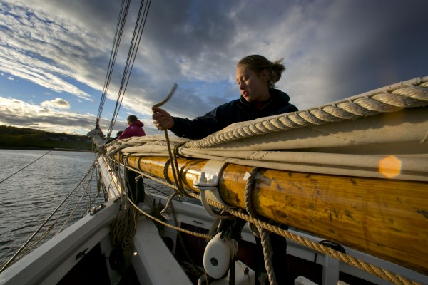 Deckhand Wendi Liebl lashes down a sail after the Mary Day dropped anchor for the night off Rockland, Maine.
