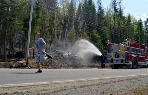 Zachary Ouellette of Fort Kent runs to move an ATV that his grandmother had parked in the road while bringing water to firefighters battling a blaze in St. Francis, Maine, on Tuesday, May 7, 2013. Ouellette was moving the ATV to make room for another tanker truck to arrive on the scene.