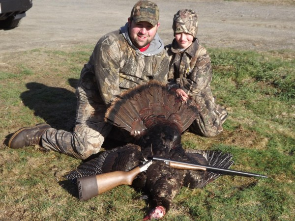 Skyler Gilbert of Brownville and his 10-year-old son, Zaine Gilbert, pose with the 15-pound wild turkey that Zaine shot while hunting in Willimantic recently. The bird sported an 8 1/4-inch beard and 5/8-inch spurs.