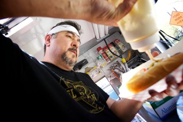 Joseph Urtuzuastegui applies the finishing touches to a Sonoran hot dog in the El Corazon food truck parked on Spring Street Wednesday. The $2.50 item comes topped with bacon, cheese, pinto beans, pico de gallo, guacamole, mayo and mustard.