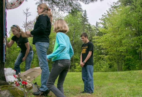 Alexis Randall, far left, a former classmate of Nichole Cable, writes messages with her family on a memorial dedicated to Cable near her home in Glenburn on Tuesday.