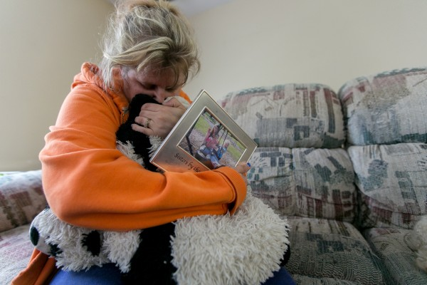 Kristine Wiley, mother of Nichole Cable, holds a picture of her daughter and hugs a pillow that belonged to Nichole at the family's Glenburn home on Tuesday.
