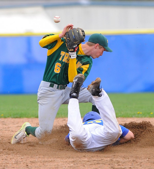 Hermon's Connor Farmer (right) dives to second base as MDI's Jon Phelps can't make the catch during the game in Hermon Thursday.