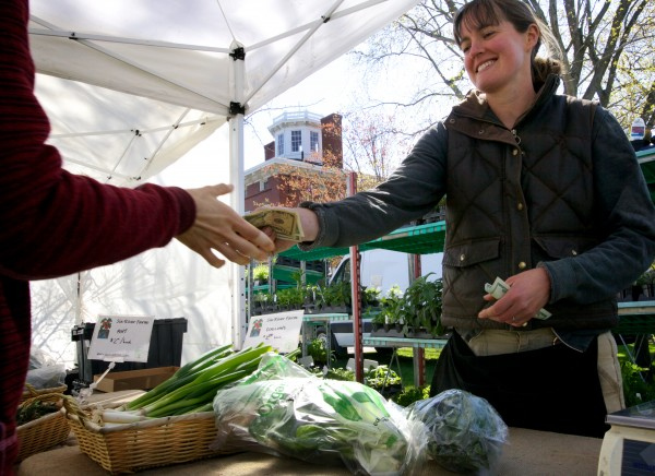 Gabrielle Gosselin makes change at her Six Rivers Farm stand at the Brunswick Farmers Market Tuesday morning. She said she doesn't get much call for it, but she'd like to accept SNAP for her produce.