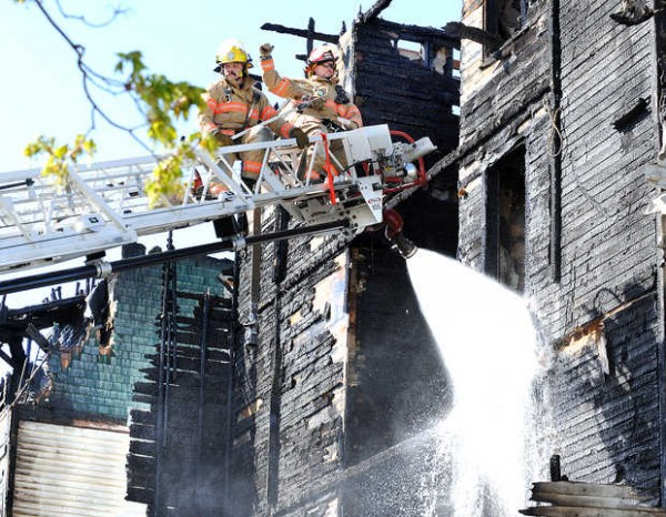 Firefighters hose down hot spots on one of two buildings on Bartlett Street that were destroyed in an early morning fire Monday.