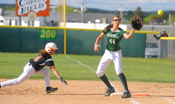 Brewer's Delaney Davis (left) dives back to first base, beating the pick-off throw to Oxford Hills' Anna Winslow, during the game in Brewer on Friday. Gabor Degre / BDN