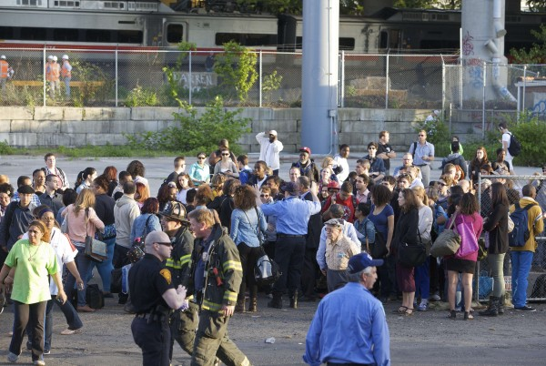 Passengers wait to be picked up by bus after two commuter trains collided in Bridgeport, Connecticut, causing one to derail injuring numerous passengers on Friday.