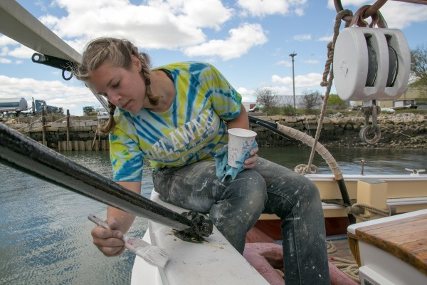 Crew member Marybeth Clay paints the stern of the coasting schooner Heritage in Rockland on Friday.