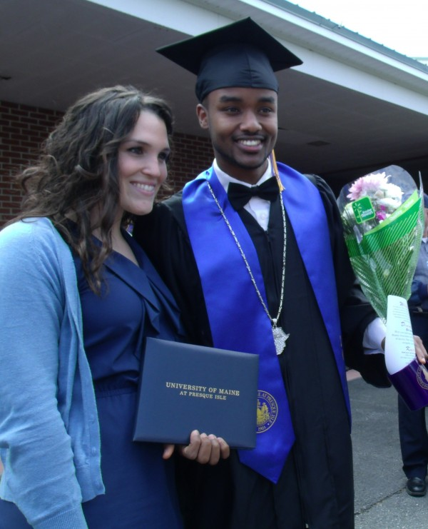 Abdigani Ashkir (right) of Portland poses with a friend while another takes their photo after commencement exercises at the University of Maine at Presque Isle on Saturday.