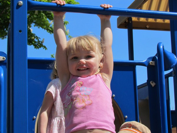 A child using her gross motor skills while on the playground.