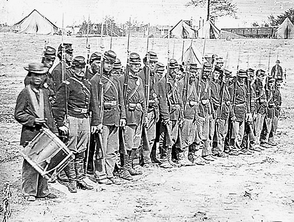 After helping capture Marye's Heights at Fredericksburg, Va. on May 3, 1863, a company of soldiers from the 6th Maine Infantry Regiment later lined up in their camp that same day to be photographed. These men had just survived a bloody charge.