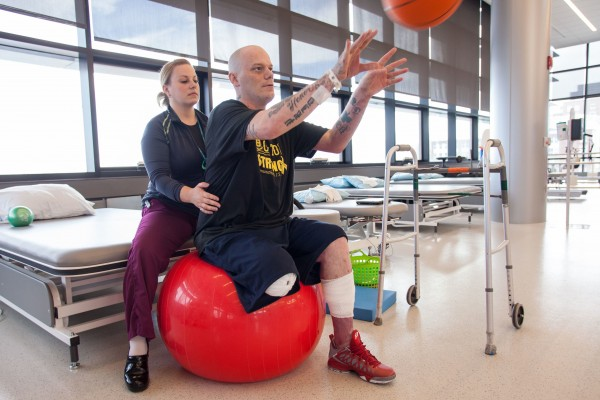 Boston Marathon bombing victim Paul Norden throws a basketball while balancing on an exercise ball during physical therapy with physical therapist Kristen Vito at Spaulding Rehabilitation Hospital in Charlestown, Mass. Norden and his brother J.P. each lost a leg in the bombing and are preparing for life as an amputee.
