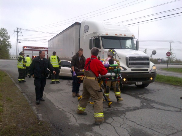 Emergency responders carry Dakota El-Hajj, 20, of Winterport from the scene of a collision between his car and a tractor-trailer on Mecaw Road in Hampden Saturday afternoon.