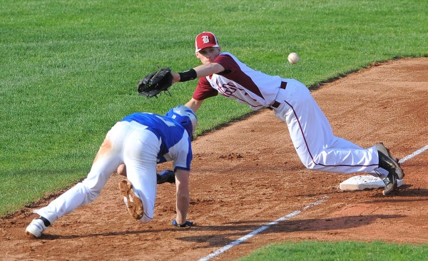 Bangor's Carl Farnham (right) dives to catch the wide throw as Lawrence's Cody Martin scrambles back to third base.