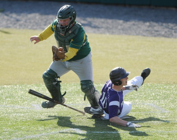 John Bapst's Andy Catlin arrives safe at home as MDI catcher Trevor Alley trips on the bat while trying to make the play at the plate on Friday at Husson University.