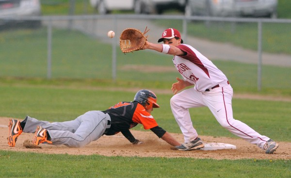 Brewer's Ben Pushard (left) dives back to first base beating the pick-off throw to Bangor's Anthony Capuano during the game in Brewer Monday evening.