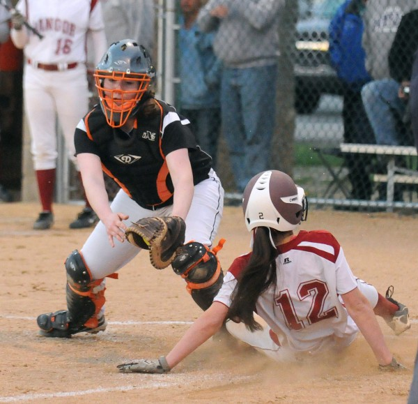 Bangor Sydni Cosgrove (right) slides to home plate beating the tag by Brewer's Samantha Pellegrino during the game in Brewer Monday.