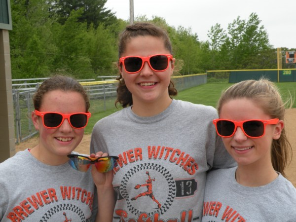 Meg Davis (left), Emily Gilmore (center) and Delaney Davis display sunglasses the Brewer High School softball team selected to wear this season. Coach Skip Estes decided there was too much variation in styles and he wanted them to be more uniform. The varsity and junior varsity players have a choice between the plastic-framed bright orange sunglasses these three are wearing and the sport sunglasses with a black-and-orange frame Meg Davis has in her left hand. Most of the varsity Witches wear the bright orange sunglasses while three wear the sport sunglasses.