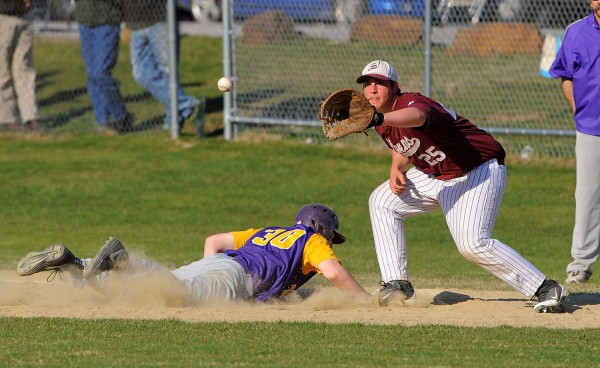 Bucksport's Gabe Stearns (left) slides to first base, beating the pick-off throw to GSA's Cooper Smallidge during the game in Bucksport on Wednesday.