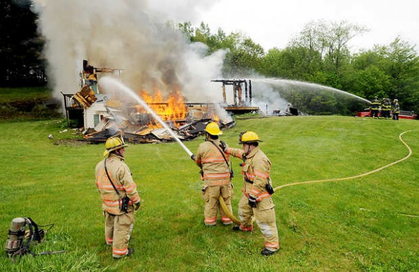Firefighters from Poland, left, and Minot, right, battle the fire at 185 Verrill Road in Minot on Friday.