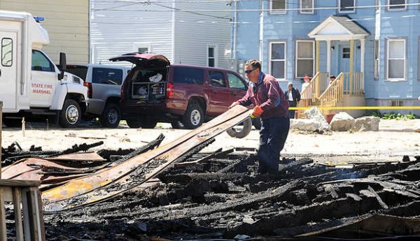 Sgt. Tim York with the state fire marshal's office sifts through debris of a four bay garage on Pierce Street In Lewiston after Friday night's fire. Three buildings, two on Pierce Street and one on Bartlett Street, were burned and a fourth on Pierce Street sustained major smoke and water damage.