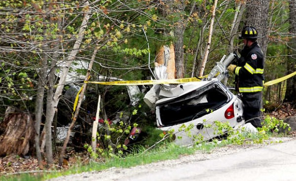 A member of the Auburn Fire Department works on the rear end of a car that ended up split in half in the trees along Garfield Road in Auburn Wednesday afternoon. Amber Brown, 25, of Minot was taken to Central Maine Medical Center after the 3 p.m. accident. The front half of the car can be seen at the left, farther into the trees.