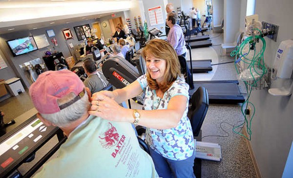 Registered nurse Heidi Langlois helps adjust the wires on Cam Cote's monitor during a Friday exercise session in the Cardiac Pulmonary Rehab Center at Central Maine Medical Center. All cardiac rehab patients' blood pressures and heart rates are monitored throughout the exercise session by a nurse. The data are examined by doctors so they can best treat patients who have had heart attacks or cardiac surgeries.