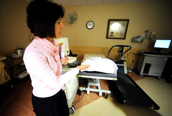 Peggy McRae, director of outpatient cardiovascular services, shows the stress test room at the Central Maine Heart and Vascular Institute. For some tests, patients exercise on the treadmill while being monitored and then quickly lie down on the bed so doctors can see how the heart reacts.