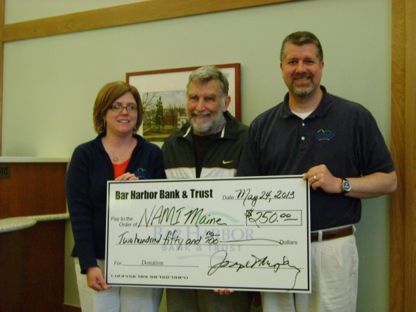 Bar Harbor Bank & Trust employees, Jody Warren (L) and Christopher Young (R), hand a sponsorship check to Chip Angell (C) for the Chris Angell Summer Classic tennis tournament being held June 1 & 2 at the Ellsworth Tennis Center, benefitting the National Alliance on Mental Illness-Maine.   For more information, to sponsor, or participate in the tournament, please contact the Ellsworth Tennis Center at 664-0400.