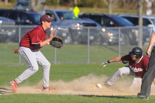 Washington Academy's Gage Feeney (right) slides to third base, beating the throw to Ellsworth's Aaron Malone during the game in Ellsworth on Tuesday.