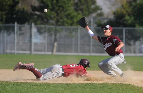 Ellsworth's Dustin Smelley (left) dives back to second base, beating the pick-off throw to Washington Academy shortstop Tyler Varney during the game in Ellsworth on Tuesday.