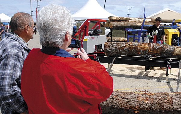As a dealer's representative demonstrates a portable sawmill, visitors to the Northeastern Forest Products Expo watch and film the event.