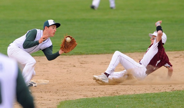 Foxcroft Academy's Forrest Law slides to second base beating the throw to Old Town's Tyler Byther during the game in Dover-Foxcroft Tuesday afternoon.