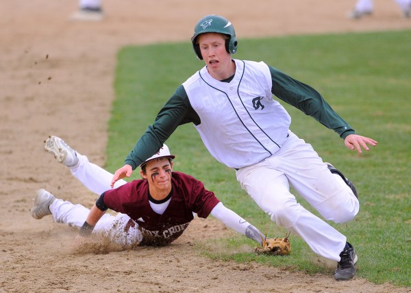 Old Town's Adam Richardson (right) runs to third base as he get past Foxcroft Academy's Caleb Richard during the game in Dover-Foxcroft Tuesday afternoon.