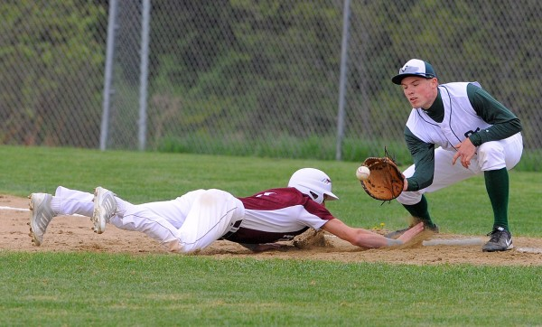 Foxcroft Academy's Hunter Law (left) dives back to first base beating the pickoff throw to Old Town's Garett Libby during the game in Dover-Foxcroft Tuesday afternoon.