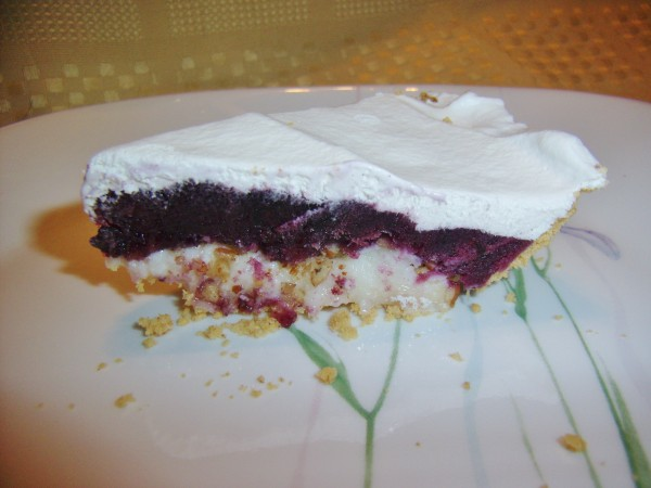 The layers in frozen blueberry pie (from the bottom) are graham cracker crust, cream cheese, chopped pecans, blueberries and whipped topping.