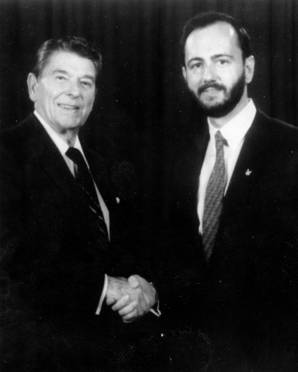 Arms dealer Rene Carlos Vos, right, posed for a picture with then-President Ronald Reagan at an event organized by the National Rifle Association.