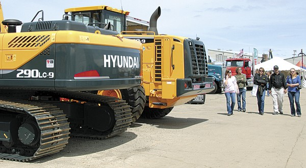 Visitors to the Northeastern Forest Products Expo walk past large logging equipment manufactured by Hyundai. The expo will be held May 17-18 at Bass Park in Bangor.
