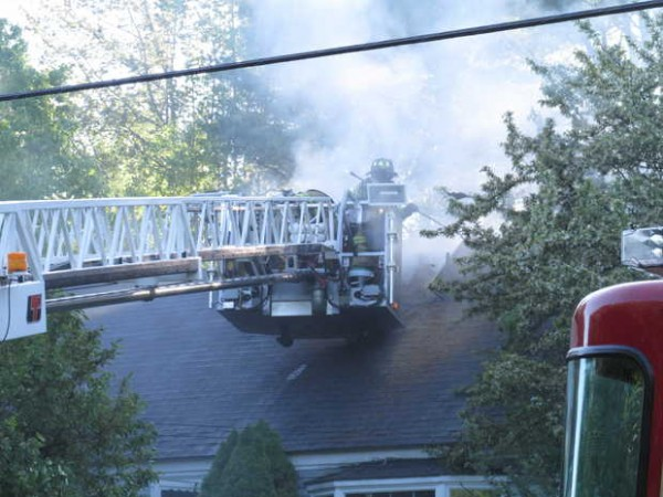 Fire crews open up the roof of a home at 226 West Gray Road. As many as 60 firefighters battled the Monday evening blaze.
