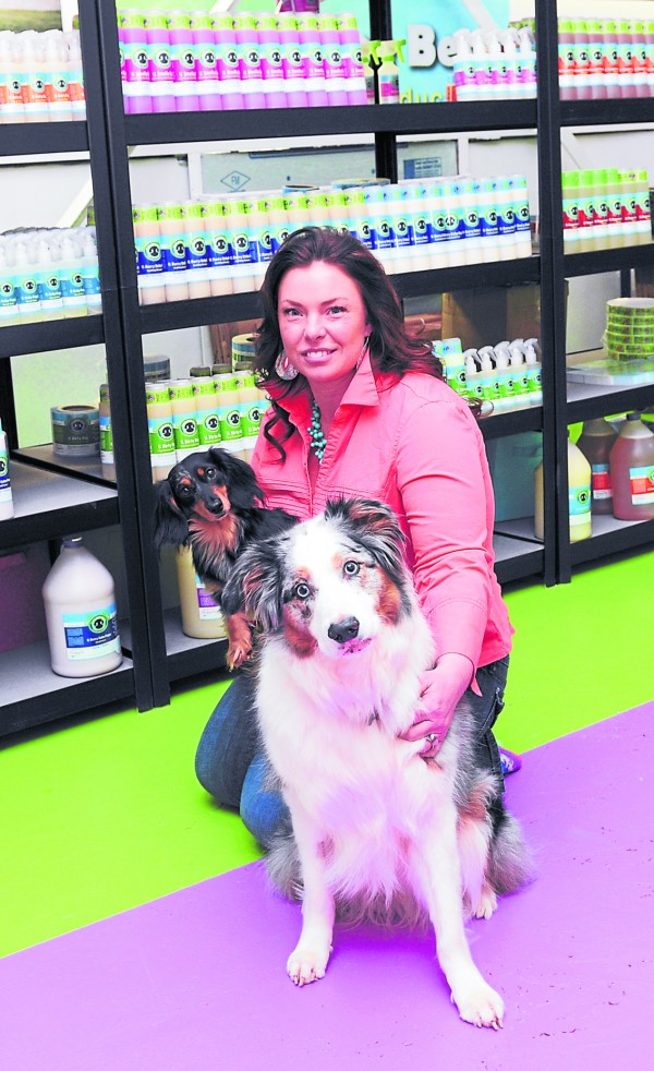 Mutt Nose Best owner Jenny Dwyer holds pets Chloe and Bandit, the face of Mutt Nose Best at the company's headquarters at 30 Bomarc Road, Bangor. The products on the shelves behind Dwyer are found in 38 states and soon will be shipped internationally.