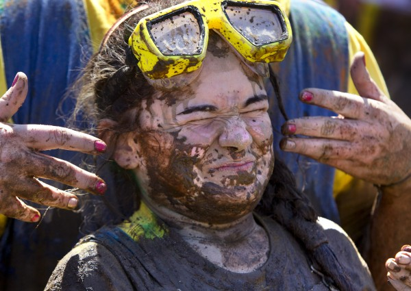Teammates smear mud onto the face of Danielle Brox, of Augusta, after she removed the goggles she wore to keep the mud out of her eyes during the Into The Mud Challenge, Sunday, April 28, 2013, in Gorham, Maine.