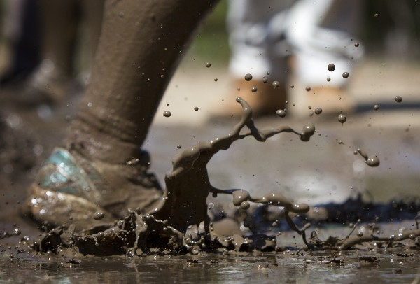 Mud splashes as a racer's shoe hits a puddle during the Into The Mud Challenge, Sunday, April 28, 2013, in Gorham, Maine.