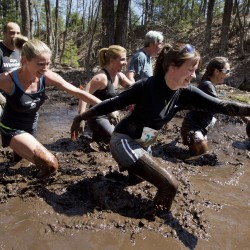 "Racers trudge through ""Got Mud,"" one of more than 20 obstacles in the Into The Mud Challenge, Sunday, April 28, 2013, in Gorham, Maine."