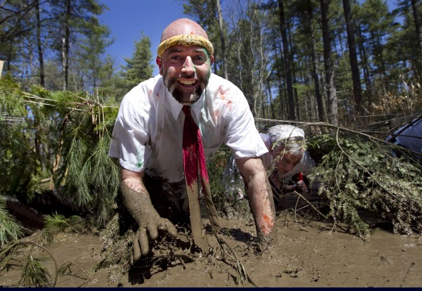 A competitor wearing a business shirt and tie emerges from the &quotCamo Crawl&quot obstacle during the Into The Mud Challenge, Sunday, April 28, 2013, in Gorham, Maine.