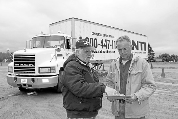 At the Northeast Technical Institute training yard on the Coldbrook Road in Hampden, CDL instructor Bob Daigle (left) explains pre-trip paperwork to Barry Wood of Old Town on May 3, 2012. Wood is enrolled in the CDL program at NTI.